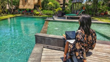 Eat, Pray, Slay in Bali starting a travel blog working on laptop by the pool